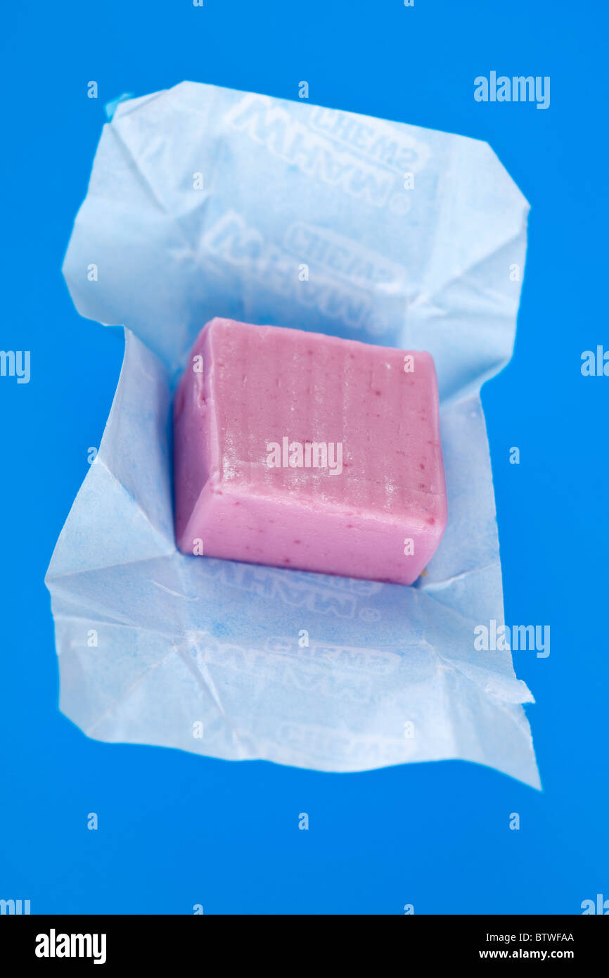 Pink sweet chew and wrapper - Stock Image