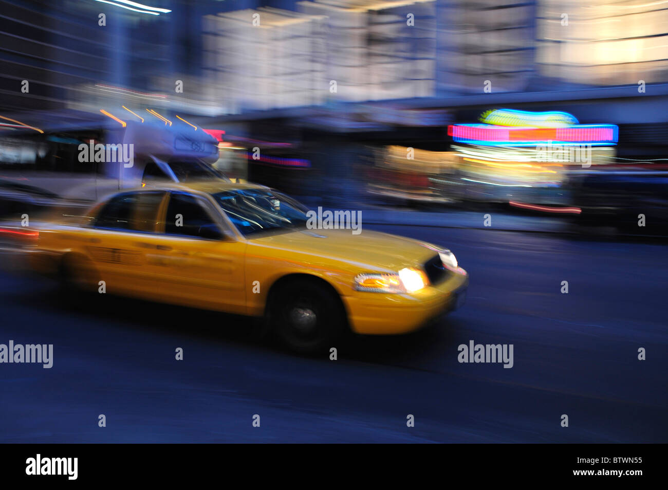 Taxicab rushing down a city street at night in a blur - Stock Image