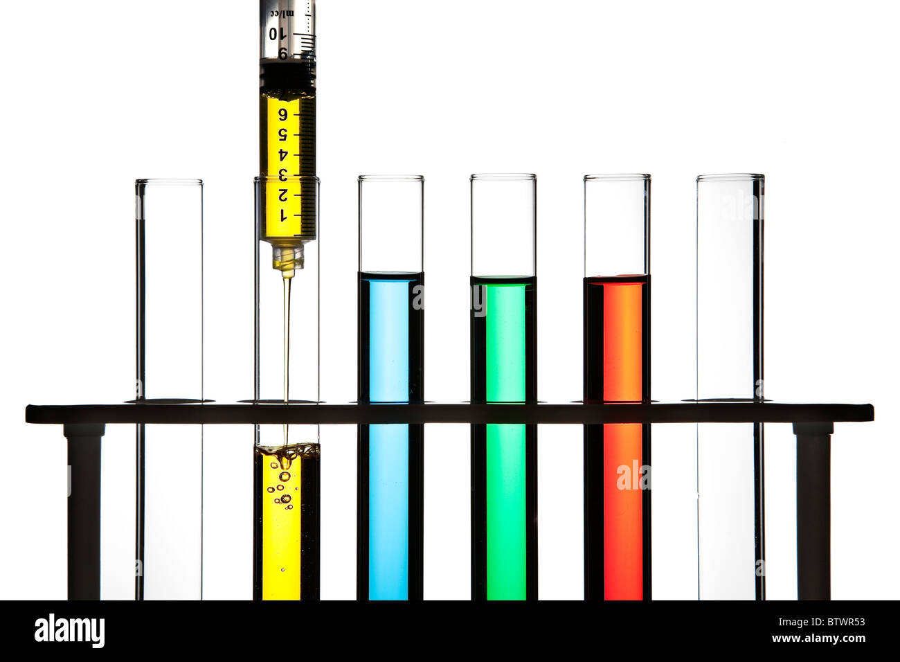 Row of test tubes filled with colored fluid, syringe filling one test tube. - Stock Image