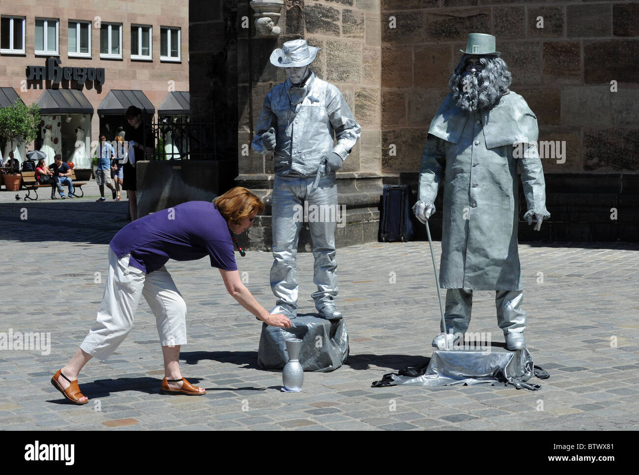 A woman contributes to mime artists performing in Nuremberg Germany Nurnberg Deutschland Europe - Stock Image