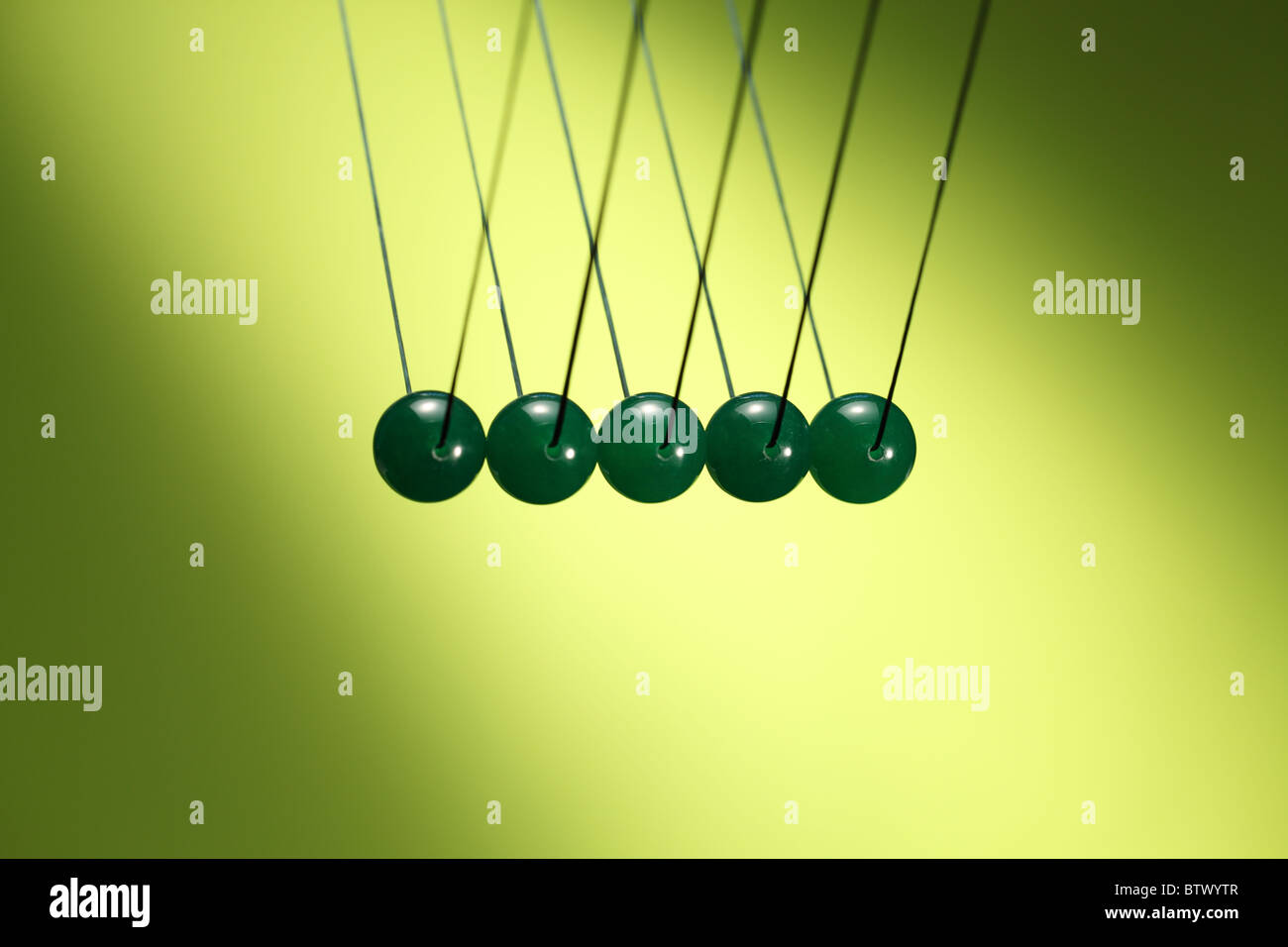 Five green marbles in row hanging from string. Illustrates Newton's cradle, a device that demonstrates conservation - Stock Image
