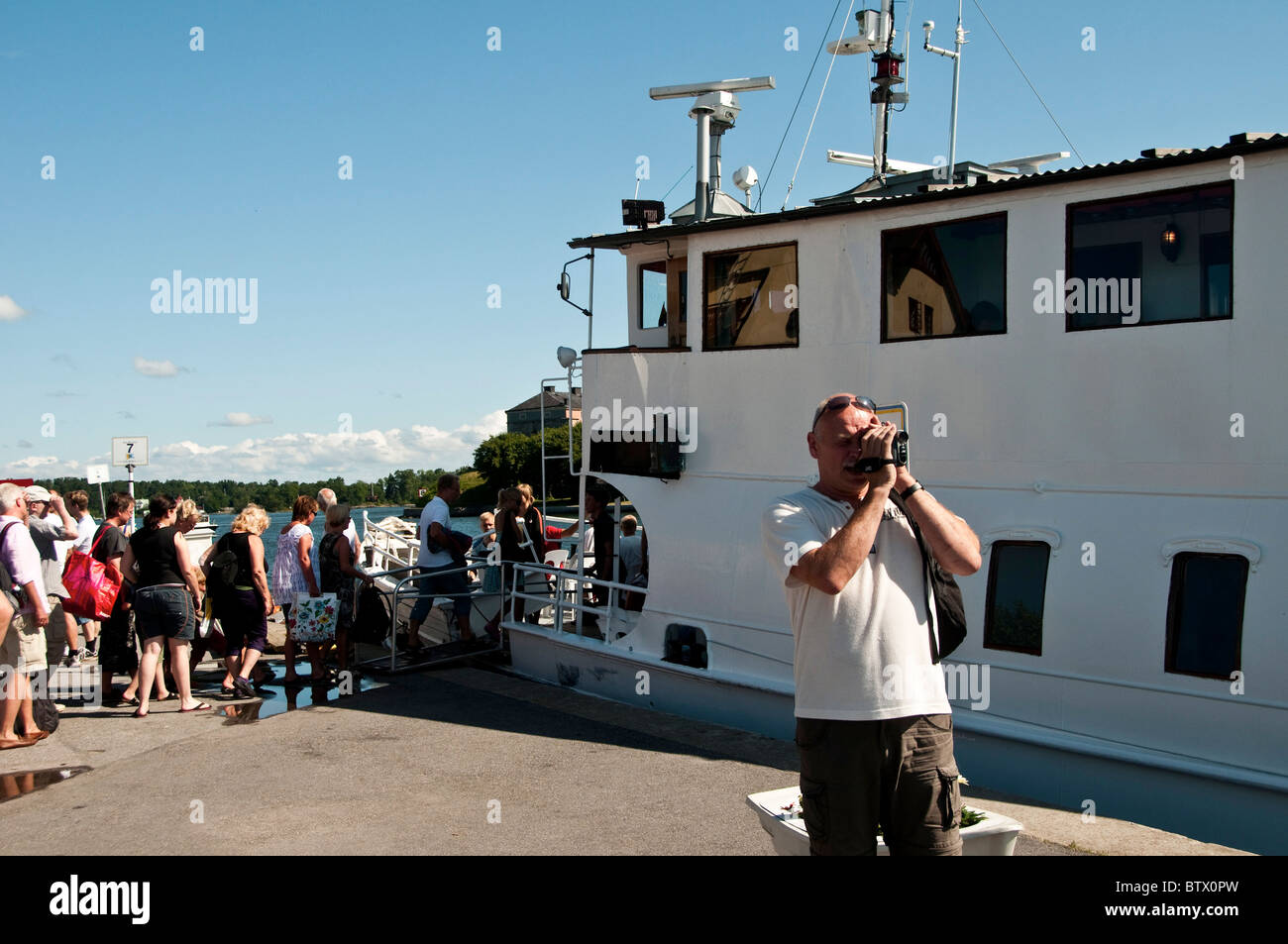Tourist embark on ferry to Stockholm from the summer town of Vaxholm in the archipelago - Stock Image