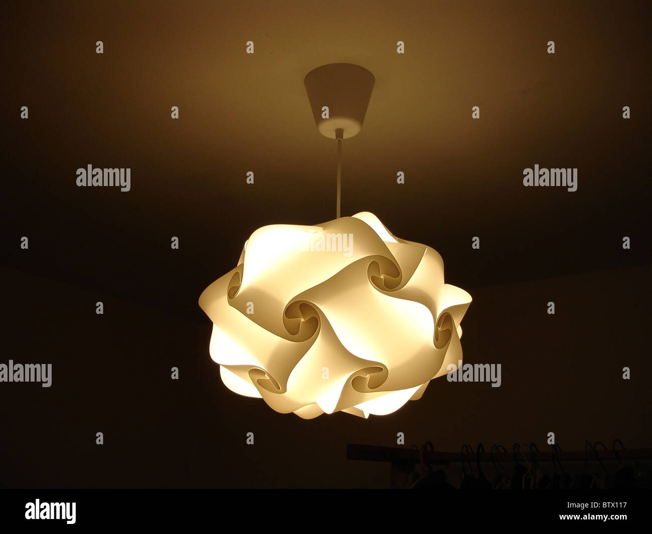 Designer lampshade suspended from ceiling with light on - Stock Image