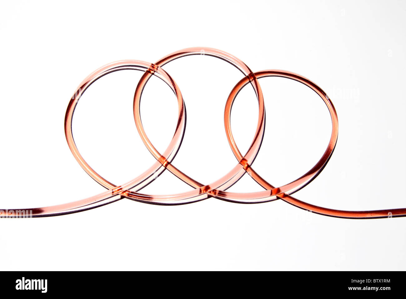 Clear rubber medical tubing with blood flowing through. Tubing is looped and twisted on itself. - Stock Image