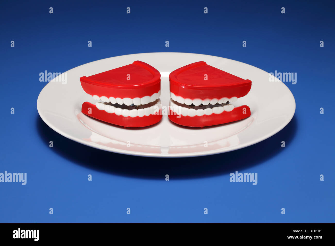 Two plastic gums and teeth on a white dinner plate - Stock Image