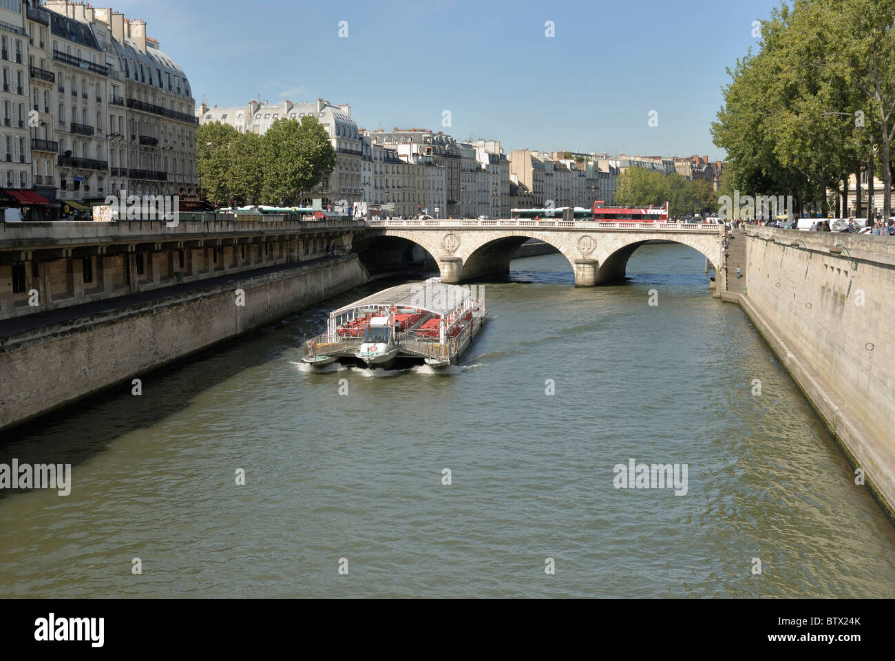 Excursion boat carrying tourists traveling down the River Seine towards Pont au Change, Paris France. - Stock Image