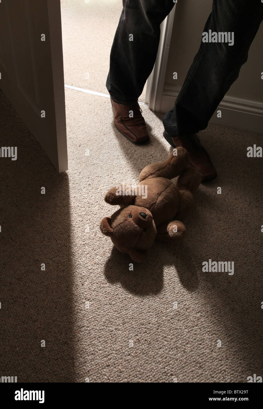 Man's legs and feett stepping past a child's teddy bear on the floor to leave the room. - Stock Image