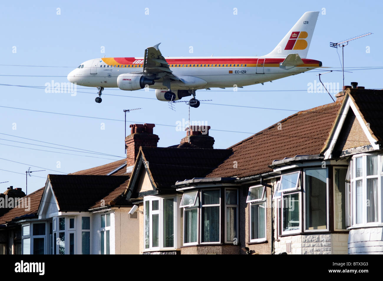 Iberia Airbus A320 approaching Heathrow runway low over Bedfont houses and rooftops, London Heathrow Airport, UK. - Stock Image