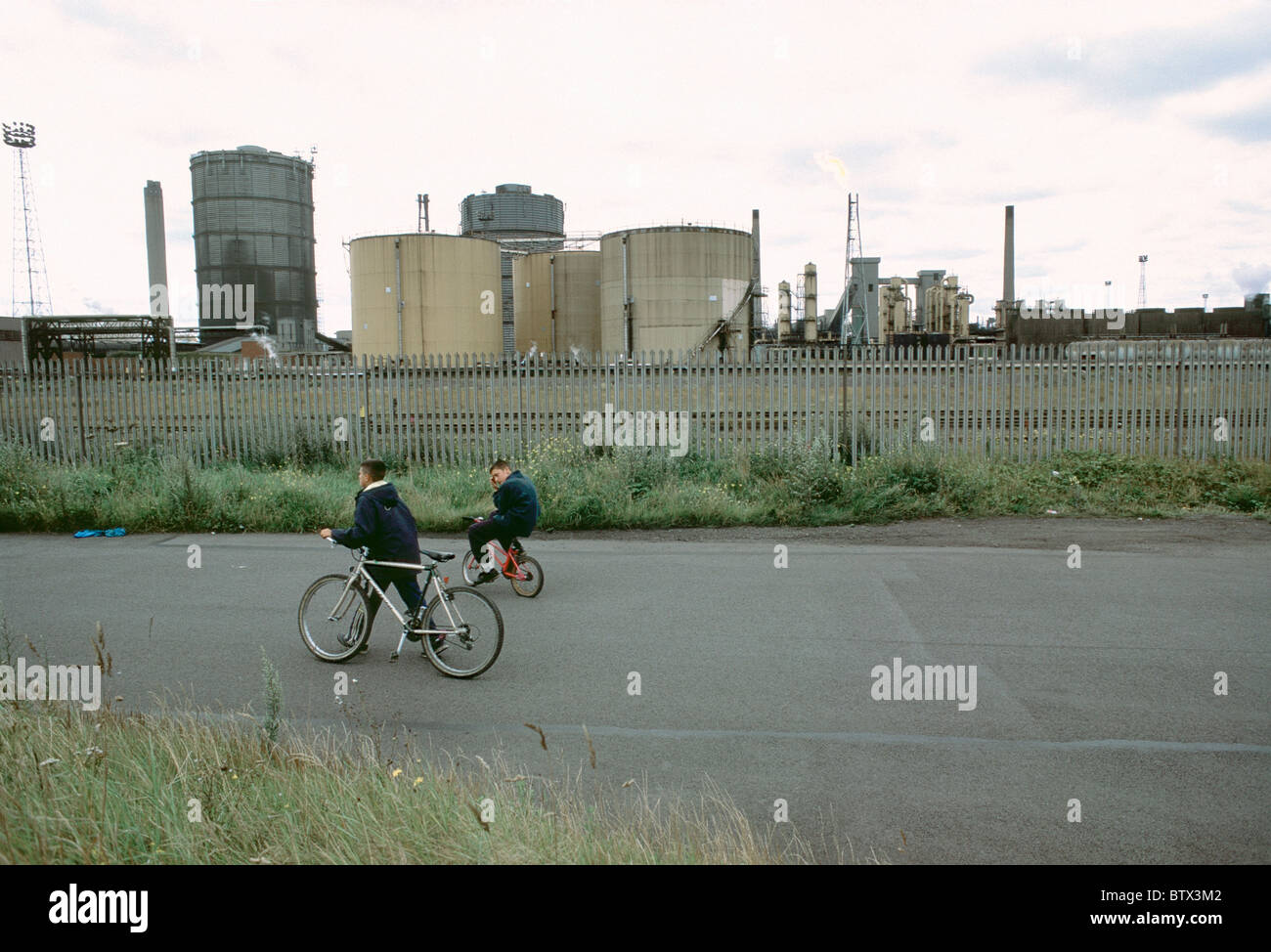 Two boys cycling past Redcar Steelworks, Teesside Stock Photo