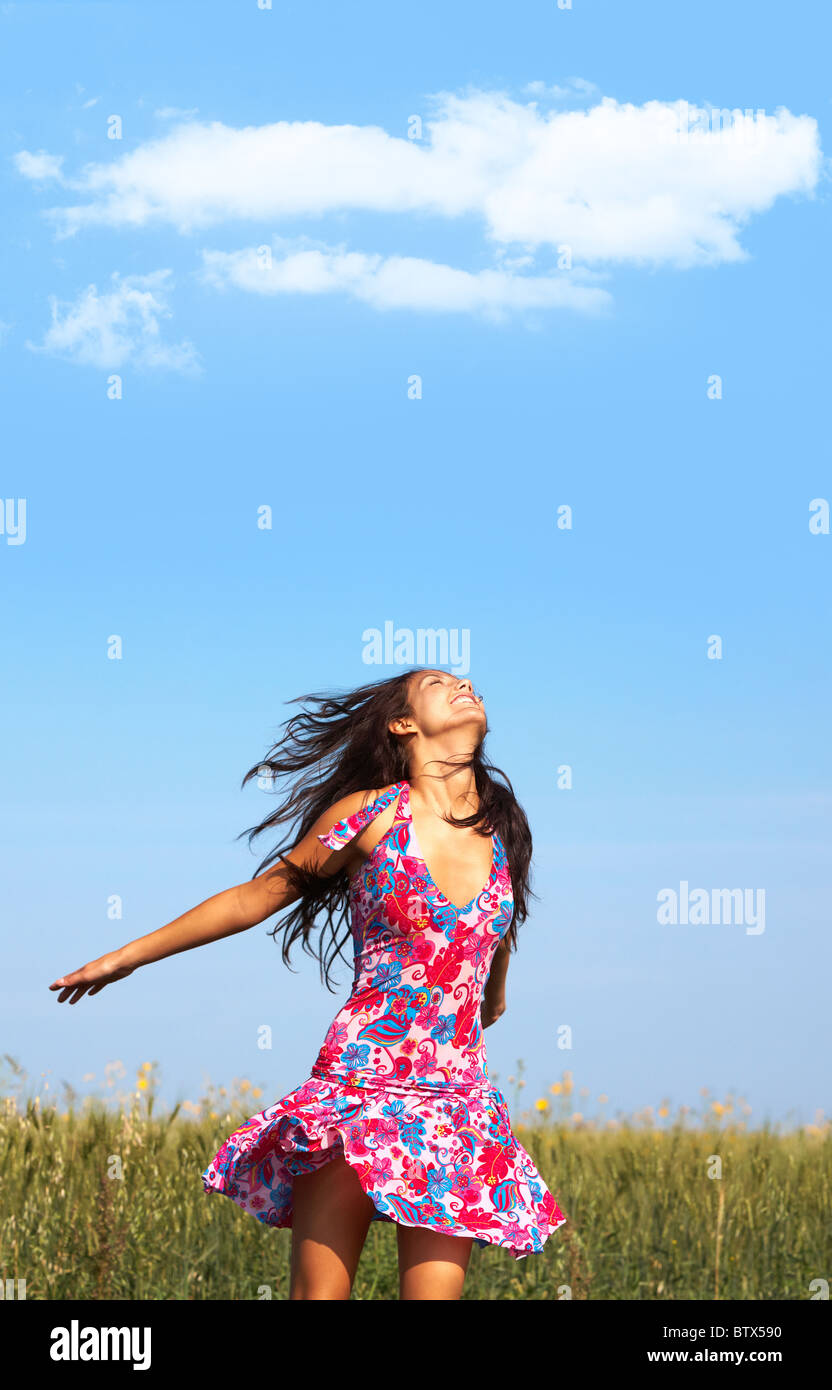 Photo of glad girl in colorful dress enjoying life in wheat meadow in summer - Stock Image