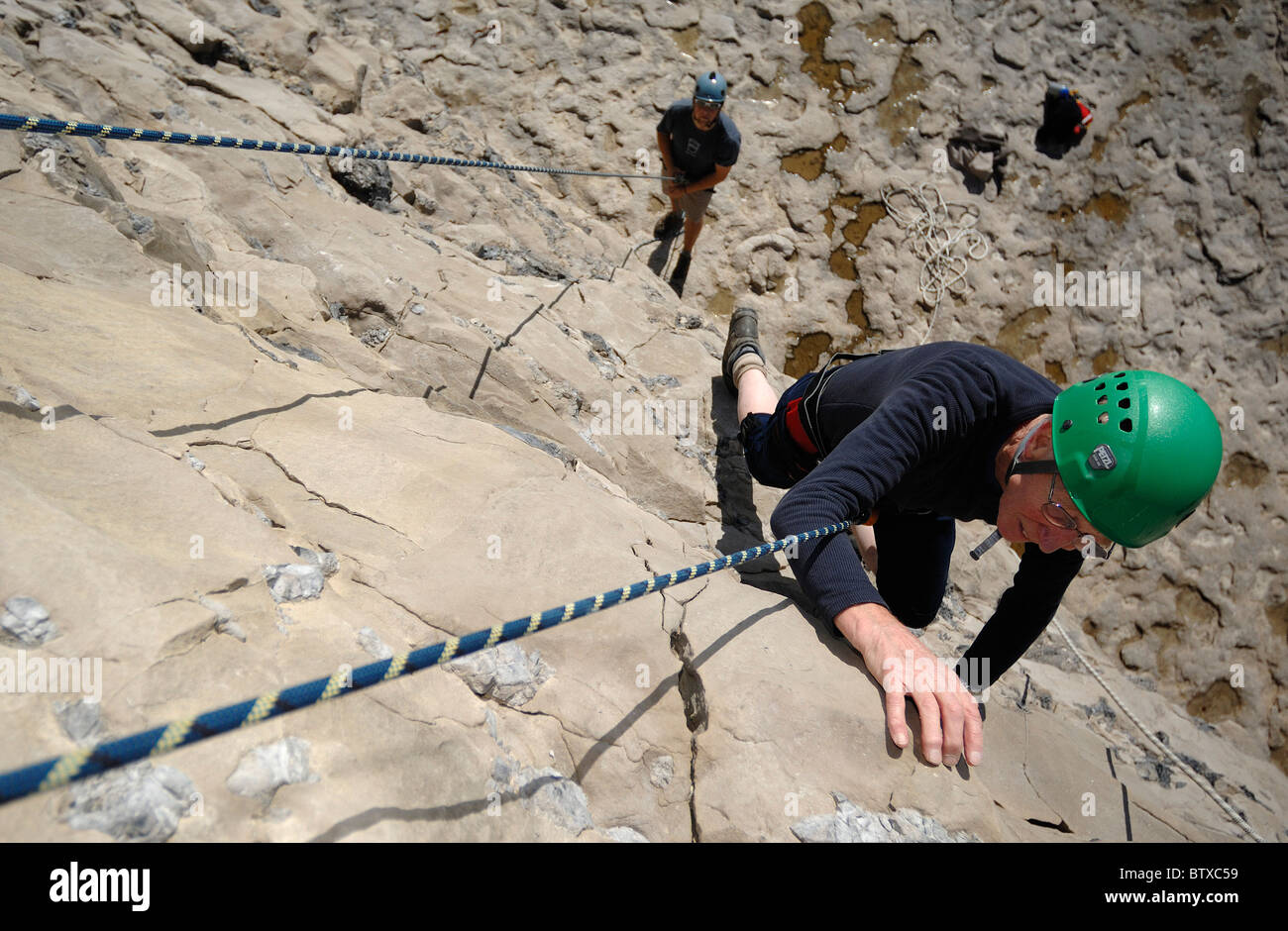 A 75 year old man learning to rock climb at Dancing Ledge Purbeck Dorset England - Stock Image