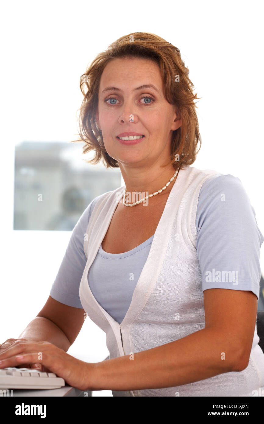 Portrait of middle-aged female typing and looking at camera Stock Photo