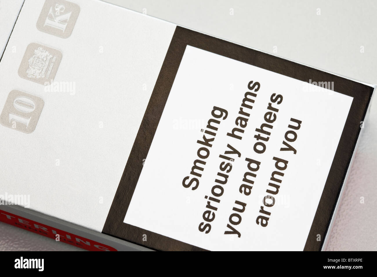 Health warning on a cigarette packet 'Smoking seriously harms you and others around you' England UK - Stock Image
