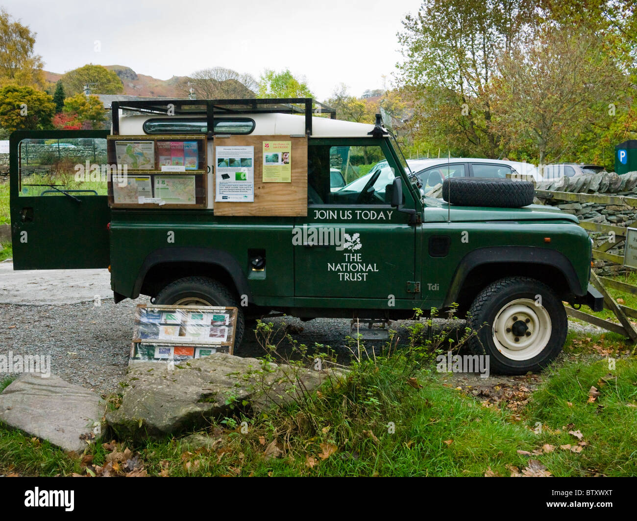 A National Trust Land Rover Defender in a car park at Elterwater in the Lake District National Park with a display - Stock Image