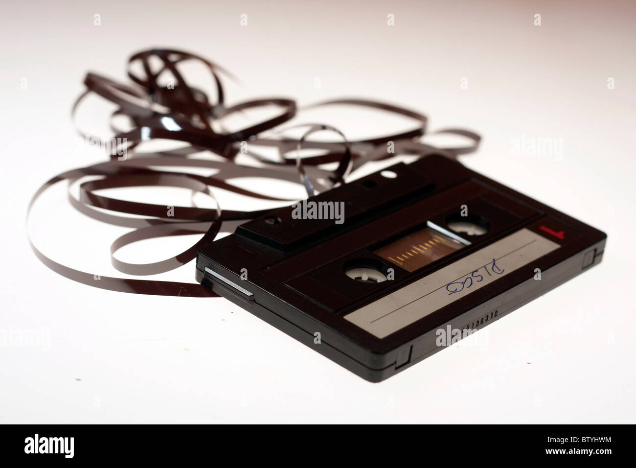 Classic audio cassette with tape isolated on white. - Stock Image