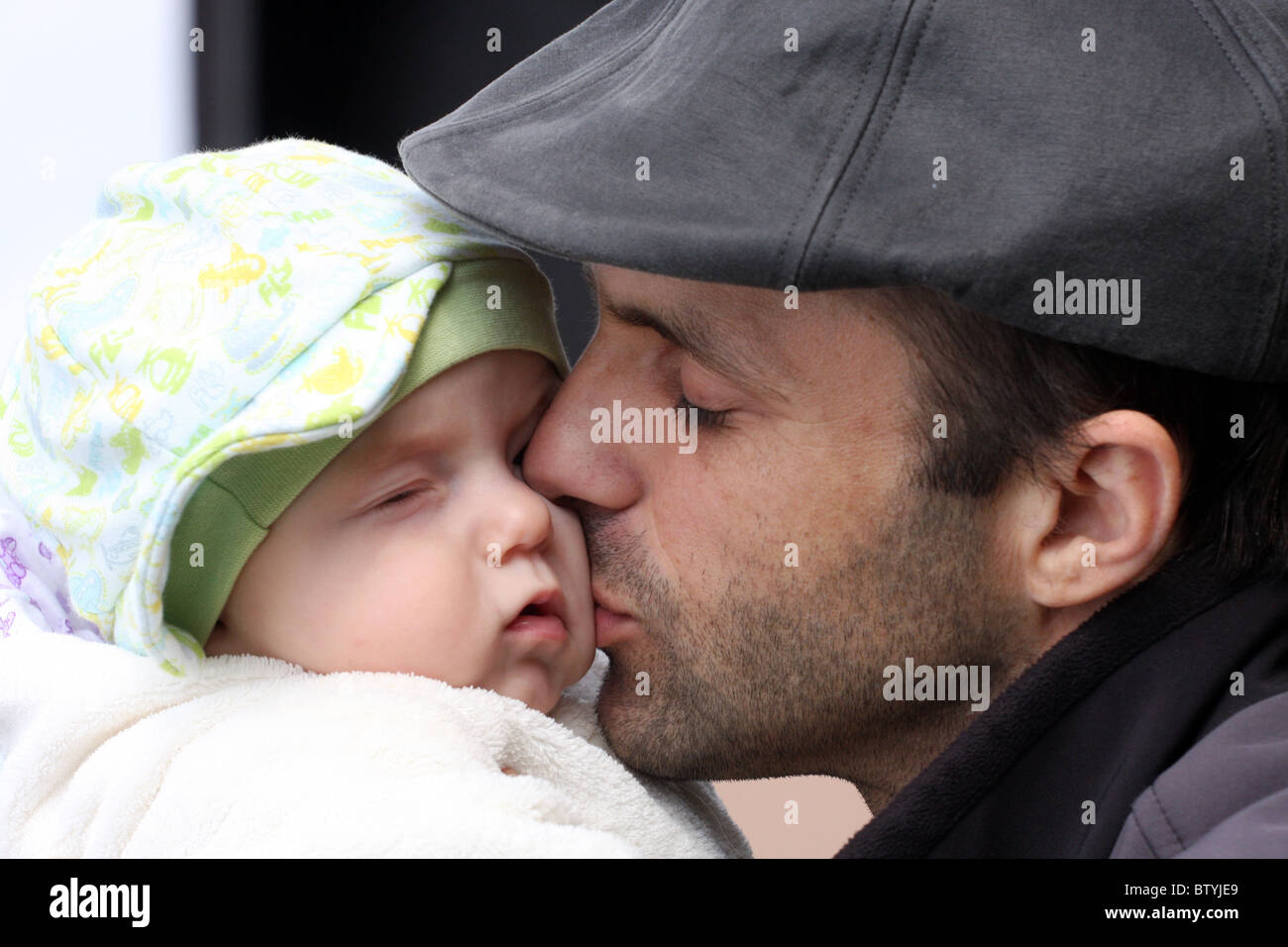 Father kissing his baby son stock image