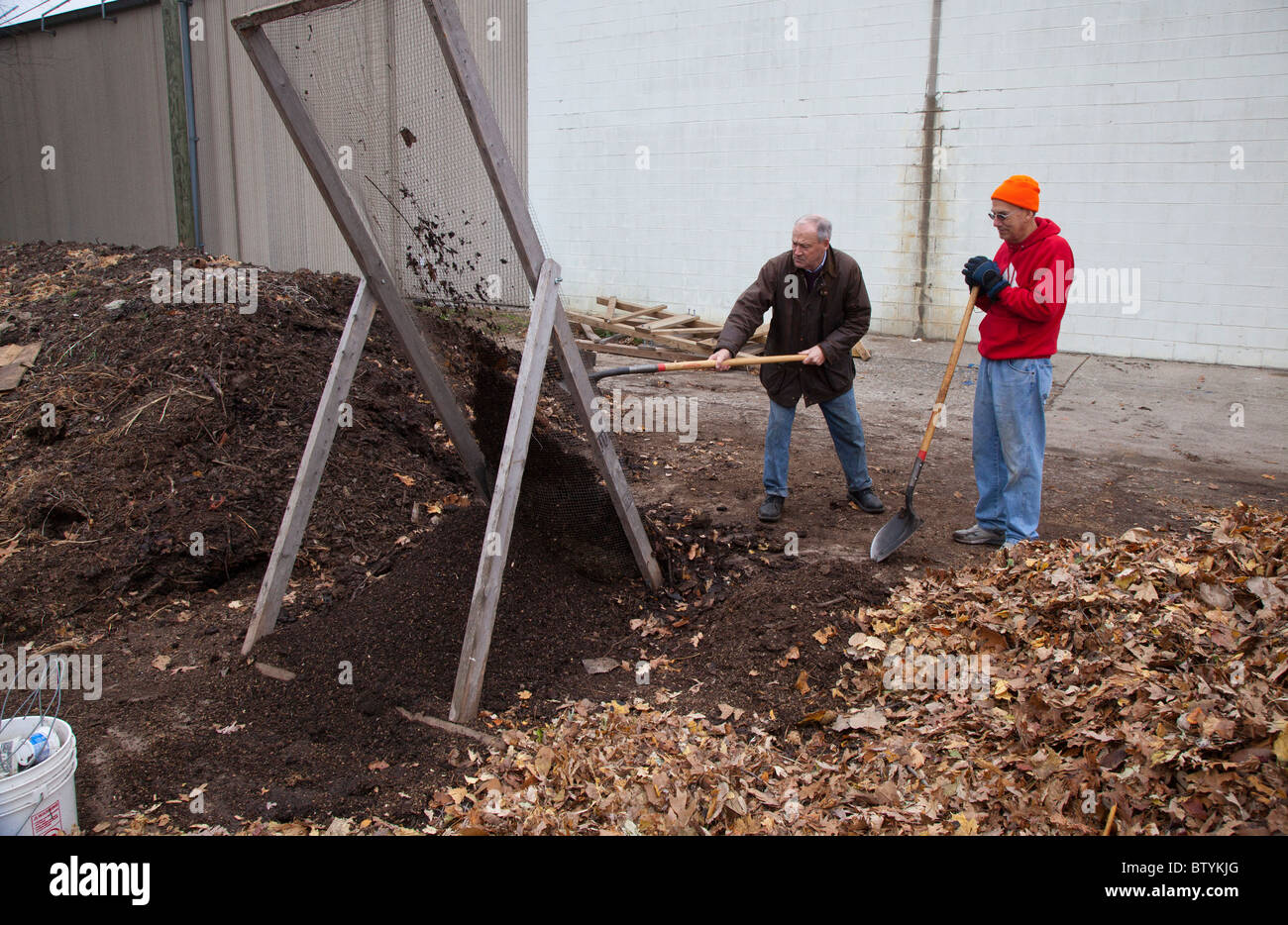 Detroit, Michigan - Two men shovel compost through a screen at the Capuchin Soup Kitchen's Earthworks Urban - Stock Image