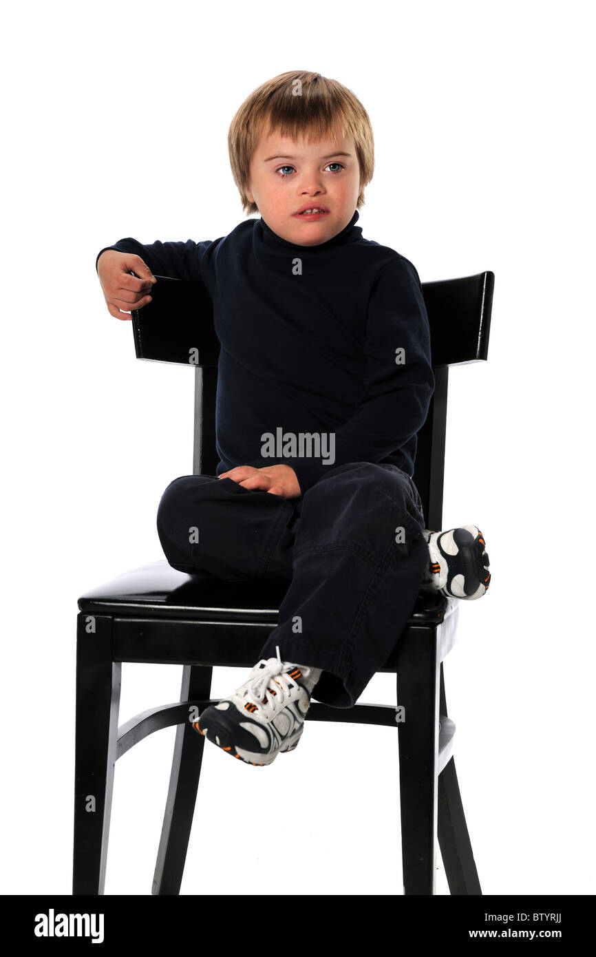 Child with Down Syndrome sitting on chair isolated over white background - Stock Image