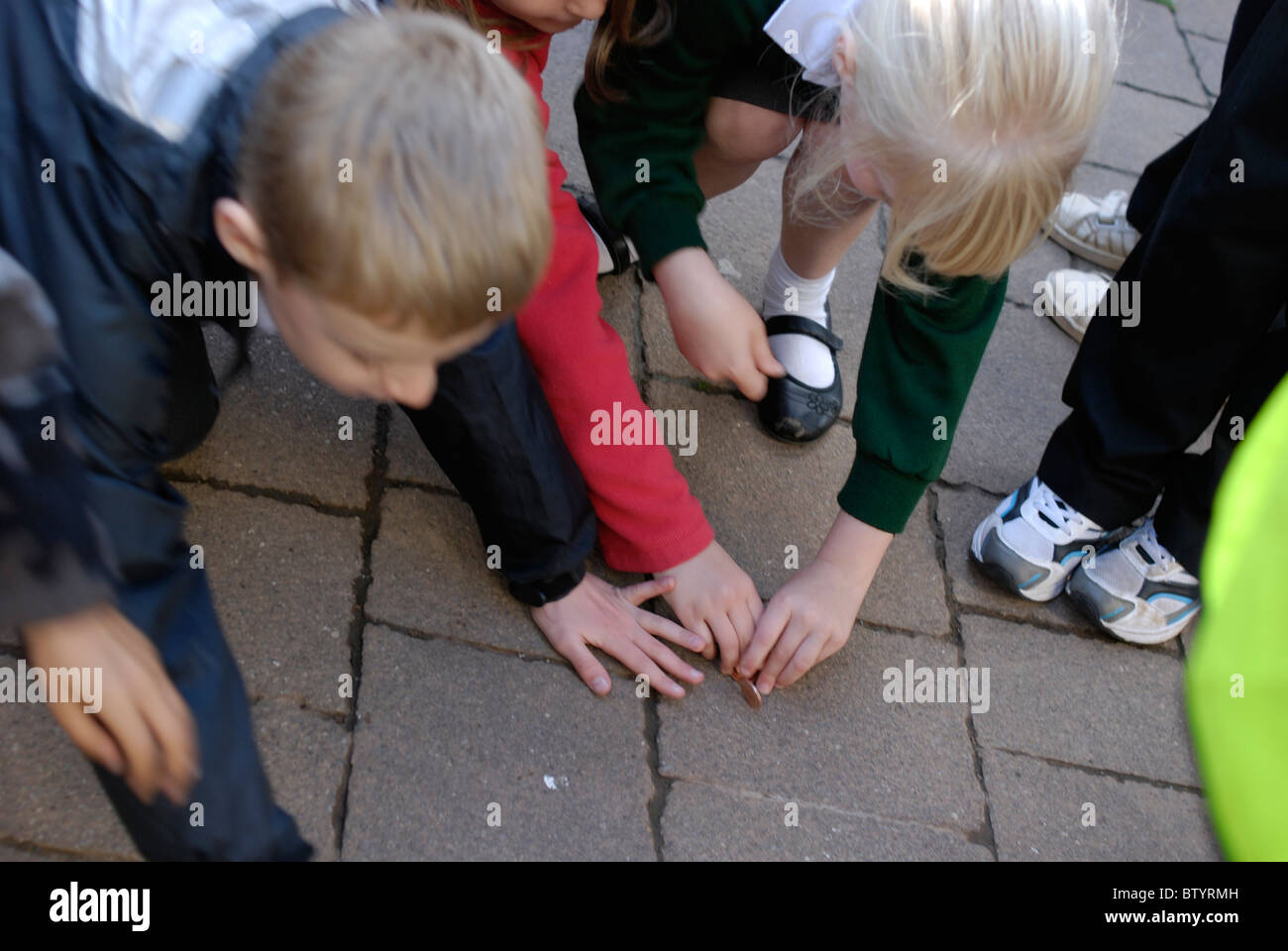 Young primary school children playing outside chasing pennies at the Tiverton Proclamation of the Fair ceremony. - Stock Image