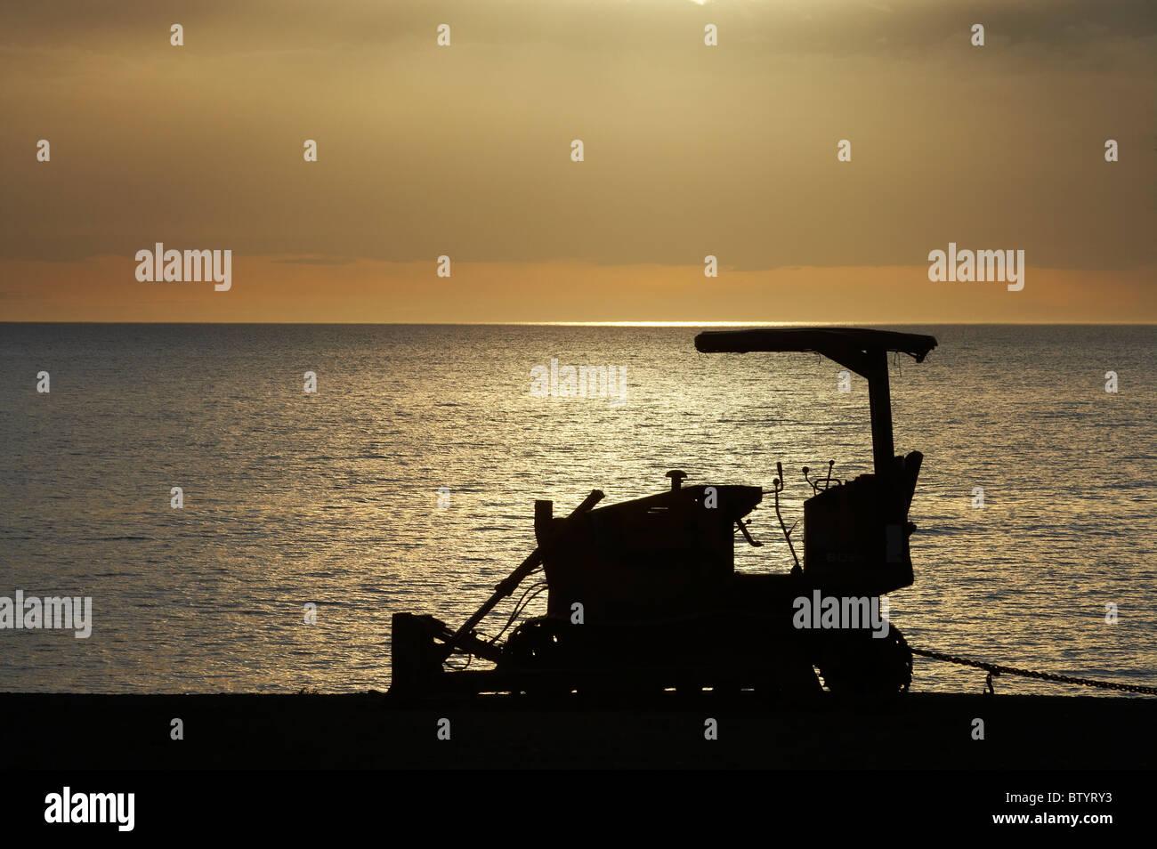 Dawn over bulldozer used for raking beach, Napier Waterfront, Hawkes Bay, North Island, New Zealand - Stock Image