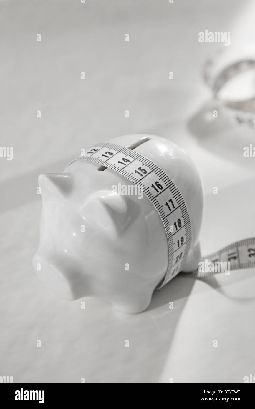 piggy bank with measuring tape around its waist - Stock Image