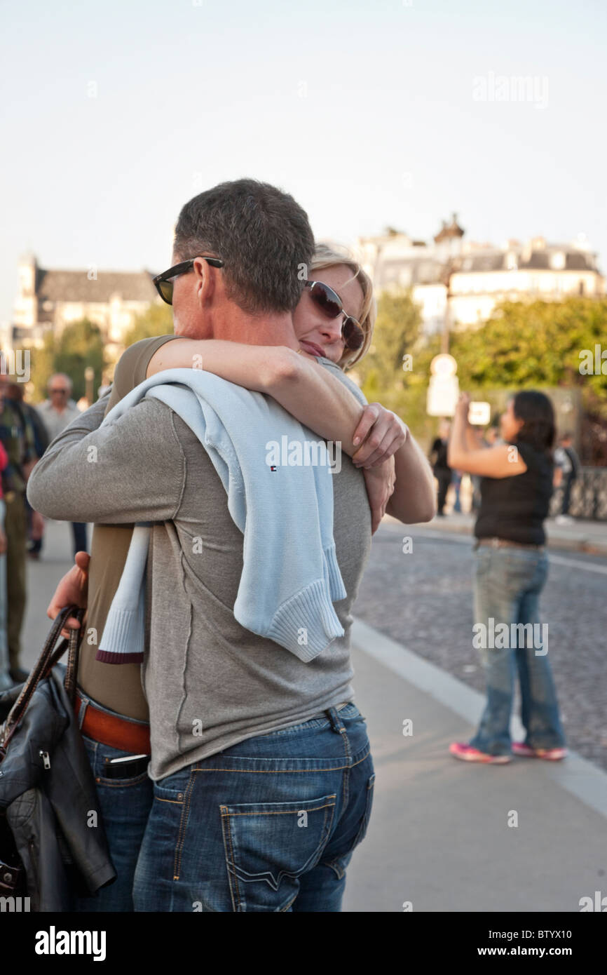 couple in spontaneous friendly embrace on Pont de l'Archeveche on beautiful warm autumn day in Paris - Stock Image