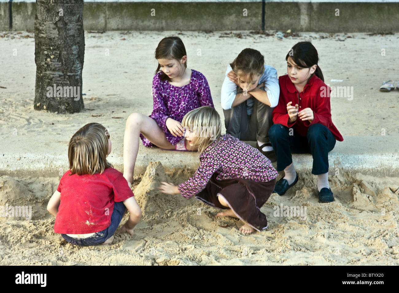 five pretty little French girls playing in sandbox in Notre Dame Cathedral park on lovely autumn afternoon Paris - Stock Image