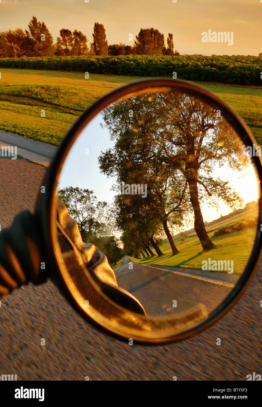 Rear view mirror of Italian scooter riding on country road. - Stock Image