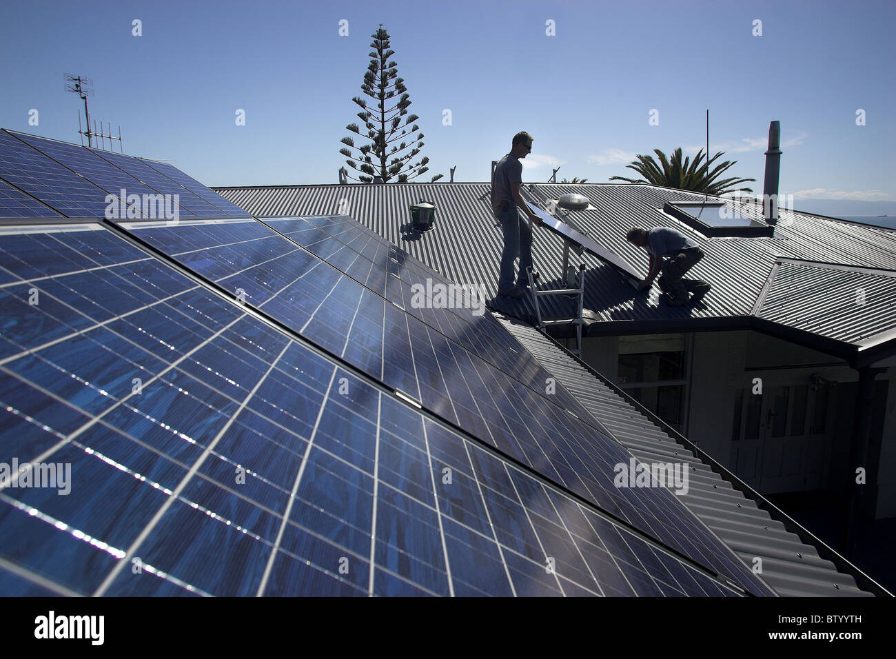 Photovoltaic solar panels being fitted by tradesmen to a house in Nelson, the city with New Zealand's highest - Stock Image