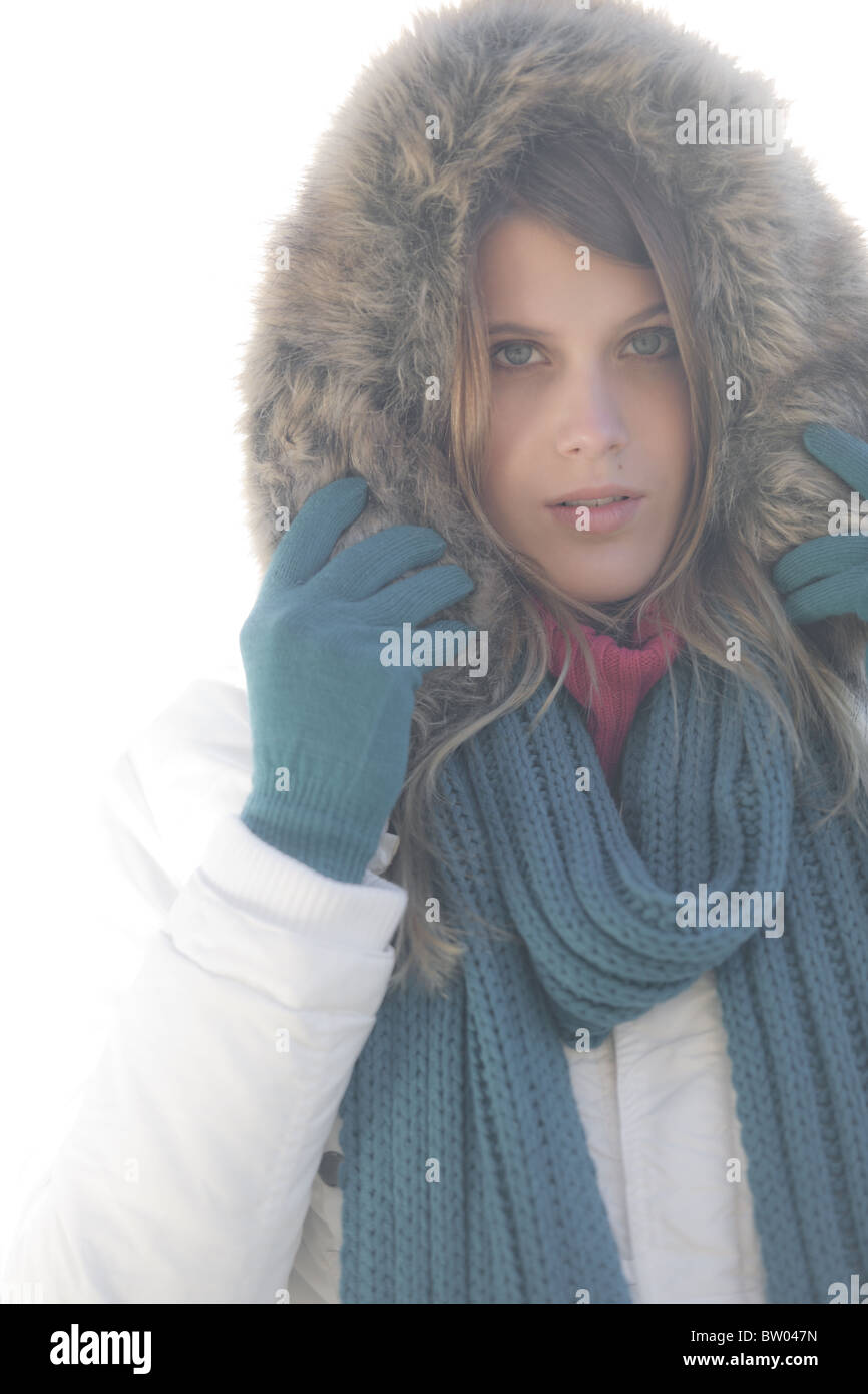 Winter fashion - woman on foggy day with fur hood, soft focus, desaturated - Stock Image