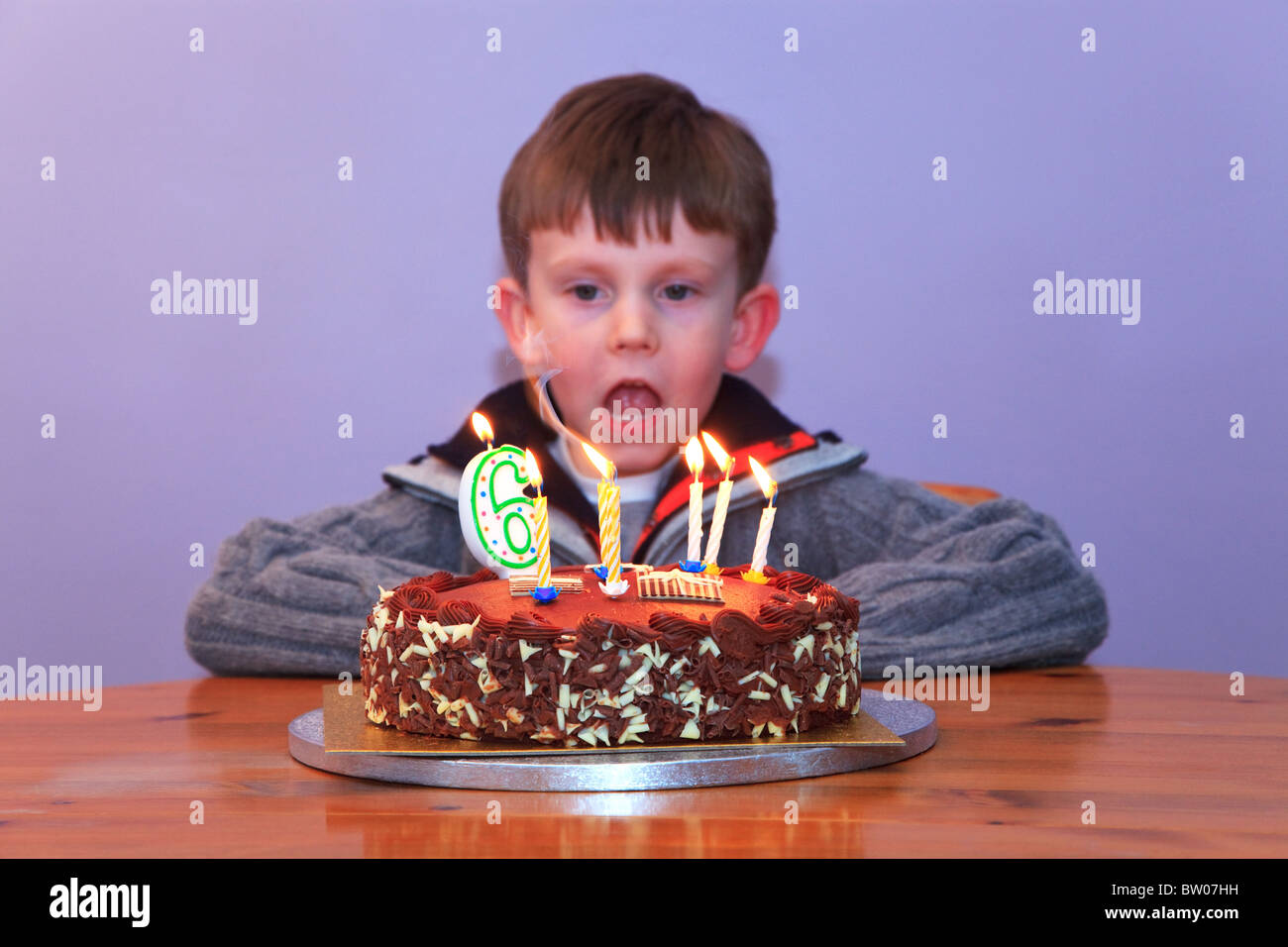 A 6 year old boy looking at the candles on his birthday cake - Stock Image