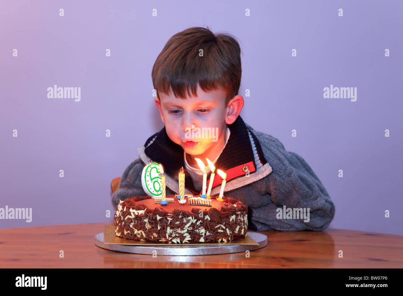 A 6 Year Old Boy Blowing Out The Candles On His Birthday Cake