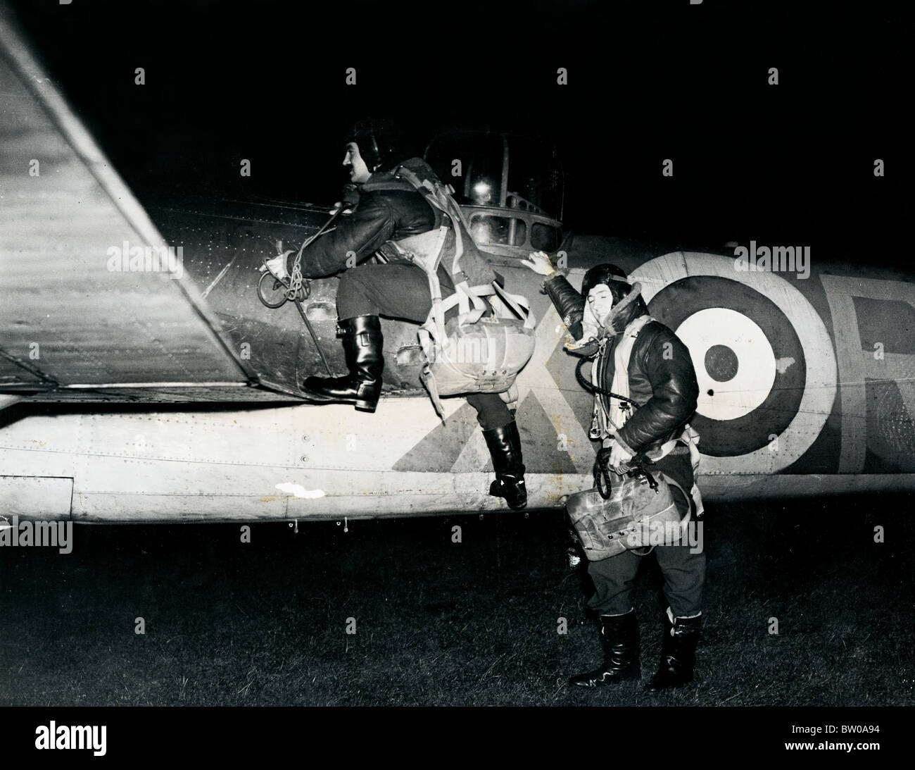 Pilot & Gunner climb into their RAF Blenheim aircraft for a night fighter patrol - Stock Image