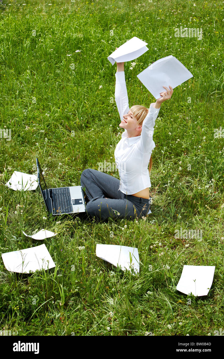 Portrait of happy woman with papers in hands sitting on green glade and raising her arms - Stock Image