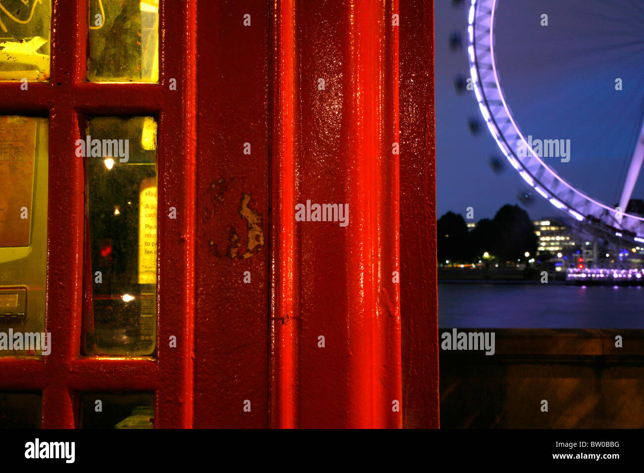 Telephone box on Victoria Embankment in front of the London Eye across the other side of the River Thames, London, - Stock Image