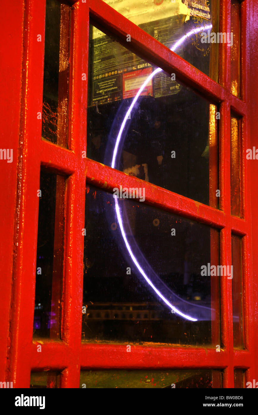 London Eye reflected in the window of a telephone box on Victoria Embankment, Whitehall, London, UK - Stock Image