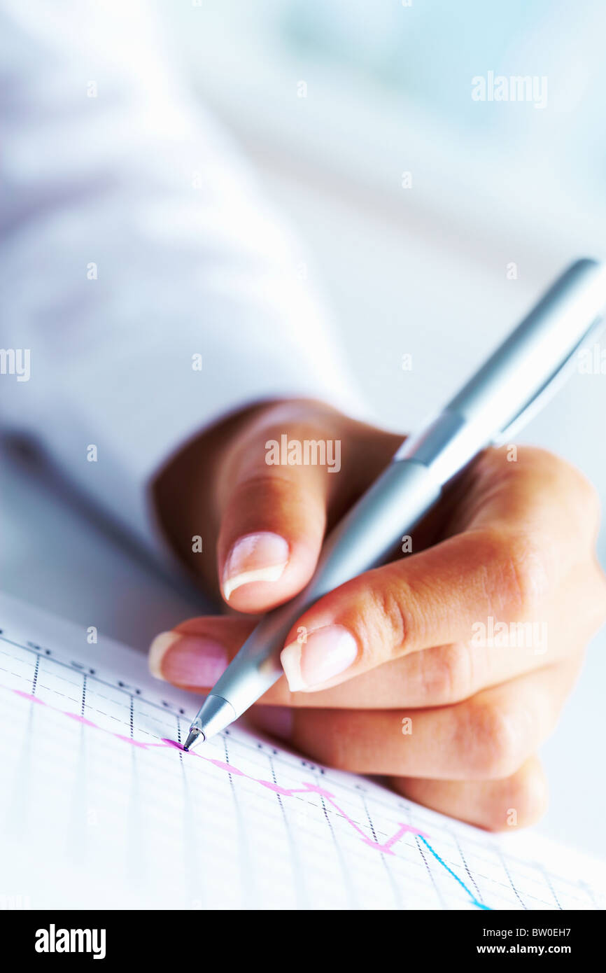 Close-up of business person hand with pen over paper - Stock Image