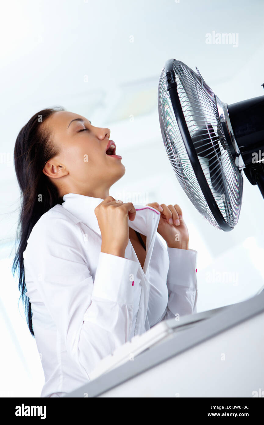 Portrait of young businesswoman enjoying fresh air stream of conditioner in office - Stock Image