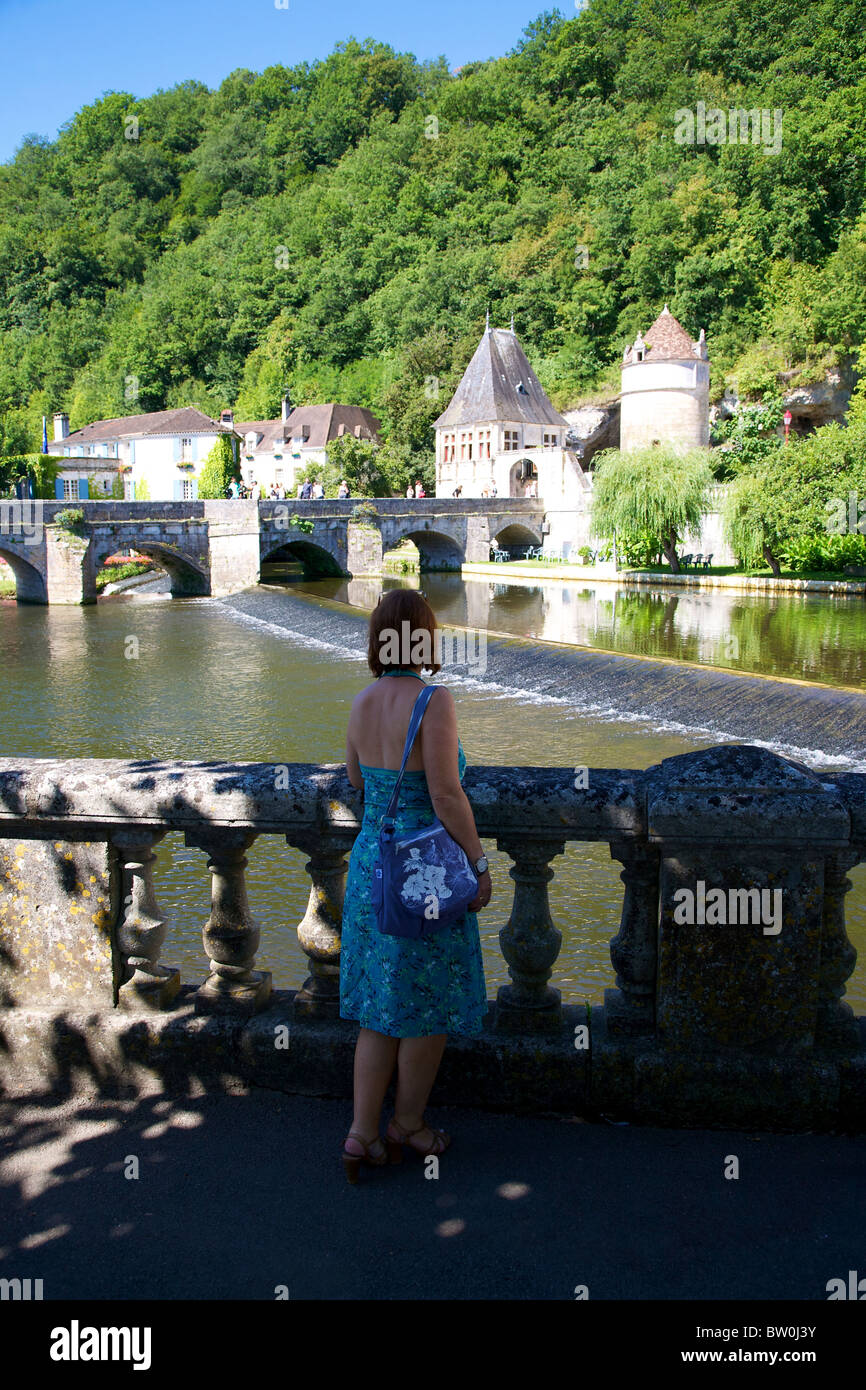 An attractive woman looking over a balustrade towards the River Dronne bridge and weir at Brantome, Dordogne, France, Stock Photo