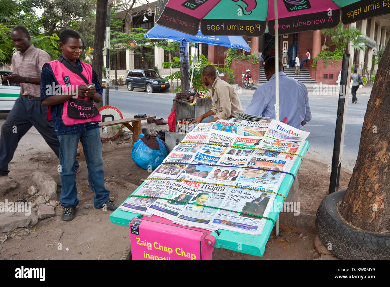 Dar es Salaam, Tanzania. Newspaper Vendor Checking his Cell (Mobile) Phone. Tanzania has many Swahili-language newspapers. - Stock Image