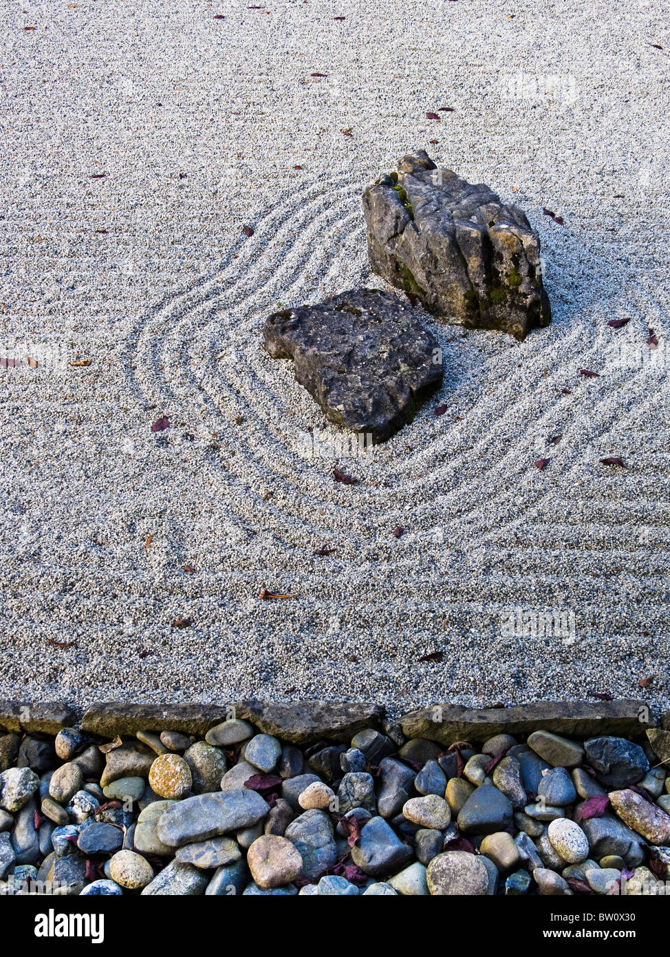 A Japanese raked gravel garden representing water with two stones and a border of pebbles - Stock Image