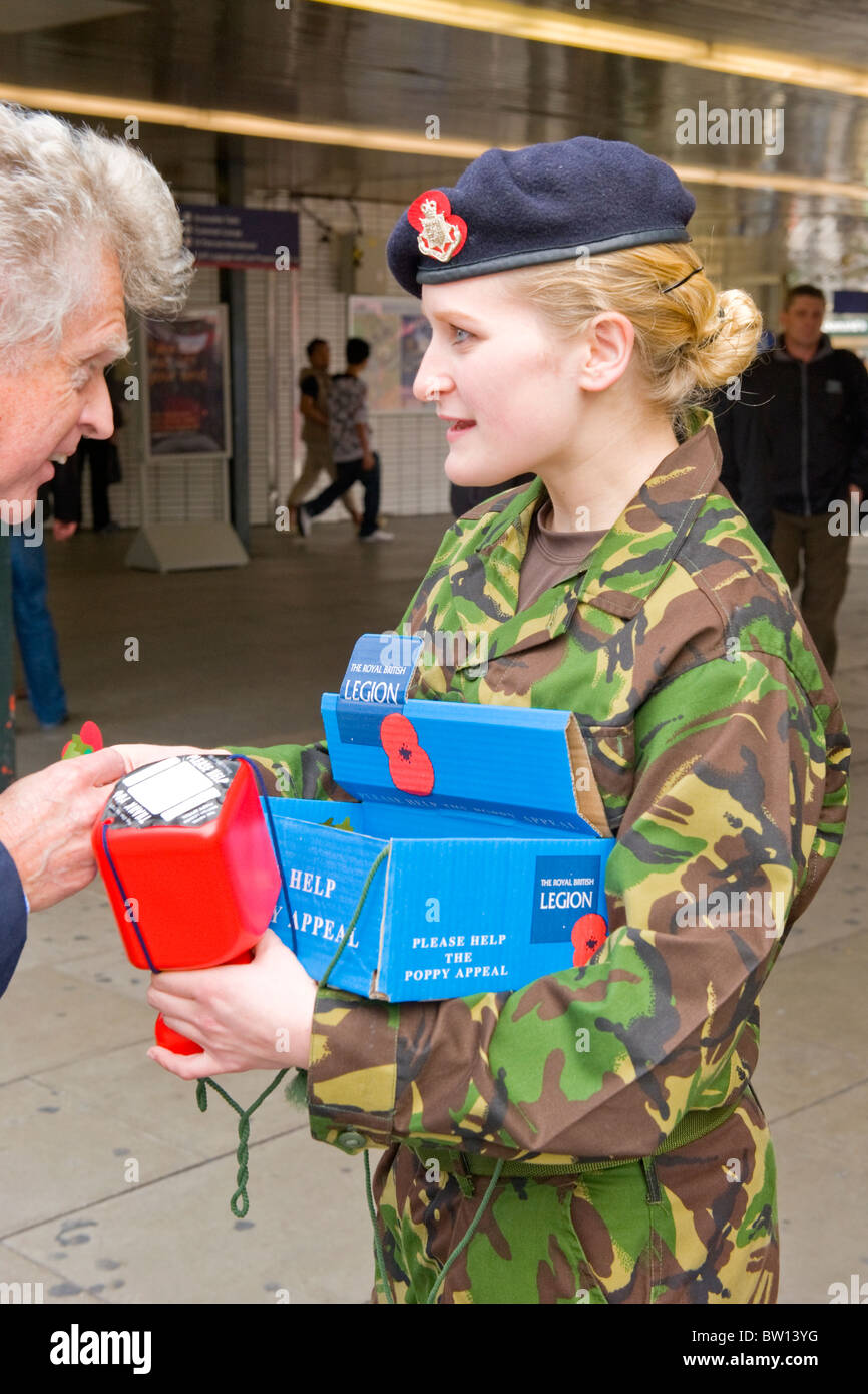 Kings Cross Station young teenage pretty girl army cadet fatigues selling Remembrance Armistice poppy Day Appeal - Stock Image