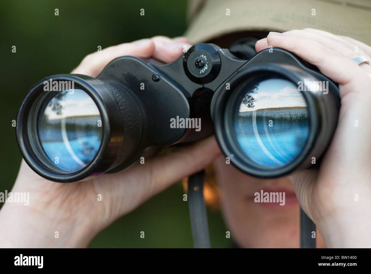 Woman looking through binoculars with reflection of a lake in the glass - Stock Image
