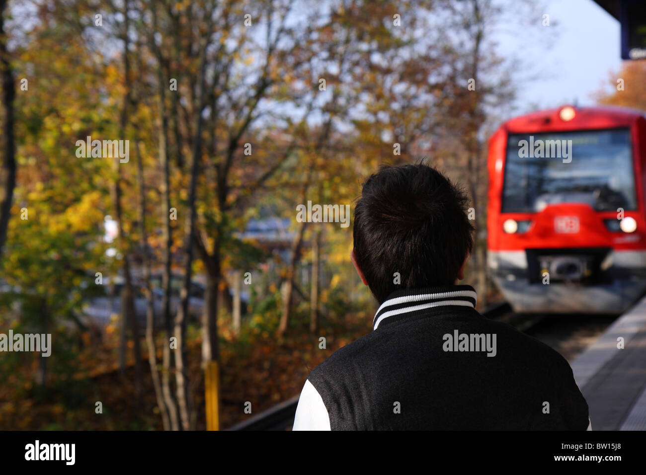 Young man waiting for a Deutsch Bahn train, which can be seen approaching, at Neuwiedenthal near Hamburg - Stock Image