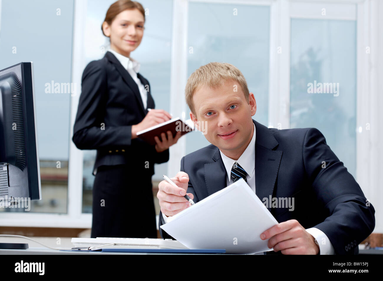 Portrait of confident boss holding papers at workplace with executive secretary standing behind - Stock Image