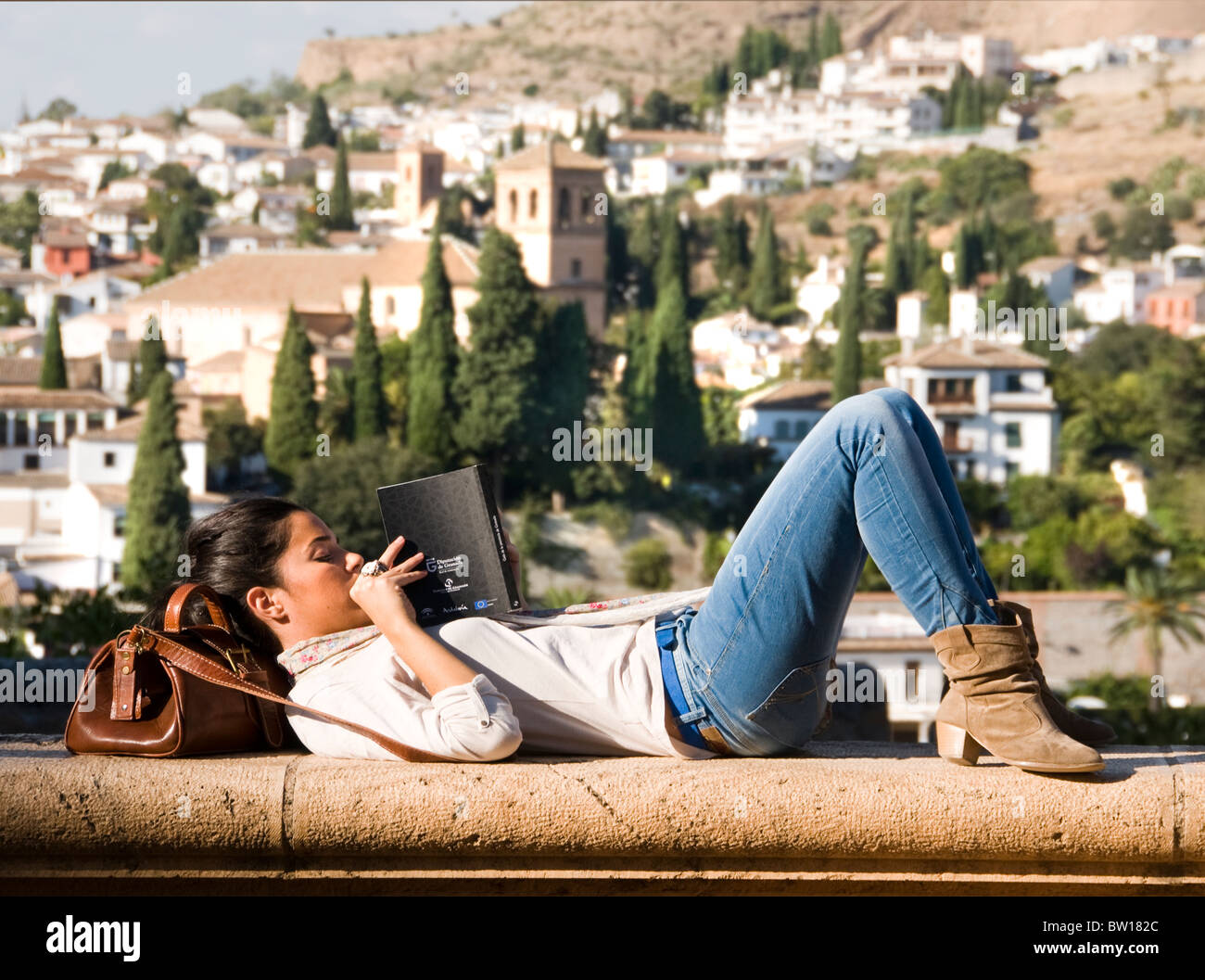 Alhambra Granada Spain Andalusia golden palace Beautiful Young Woman Student Teenager reading a Book travel guide - Stock Image