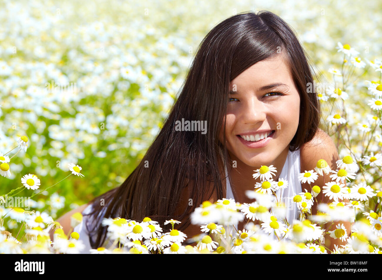 Image of happy female peeking out of chamomile glade and smiling at camera - Stock Image