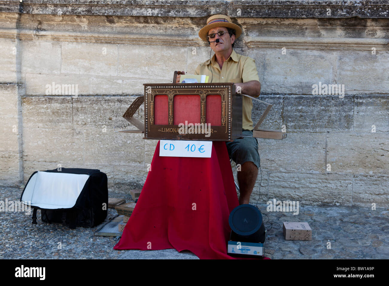 A street musician sings to the accompaniment of a Limonaire Fournier folded paper organ in Avignon, France. - Stock Image