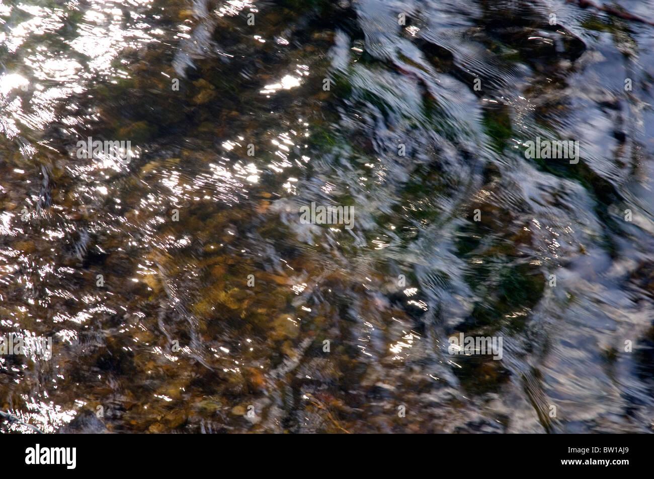 Dappled sunlight on a Flowing Stream - Stock Image