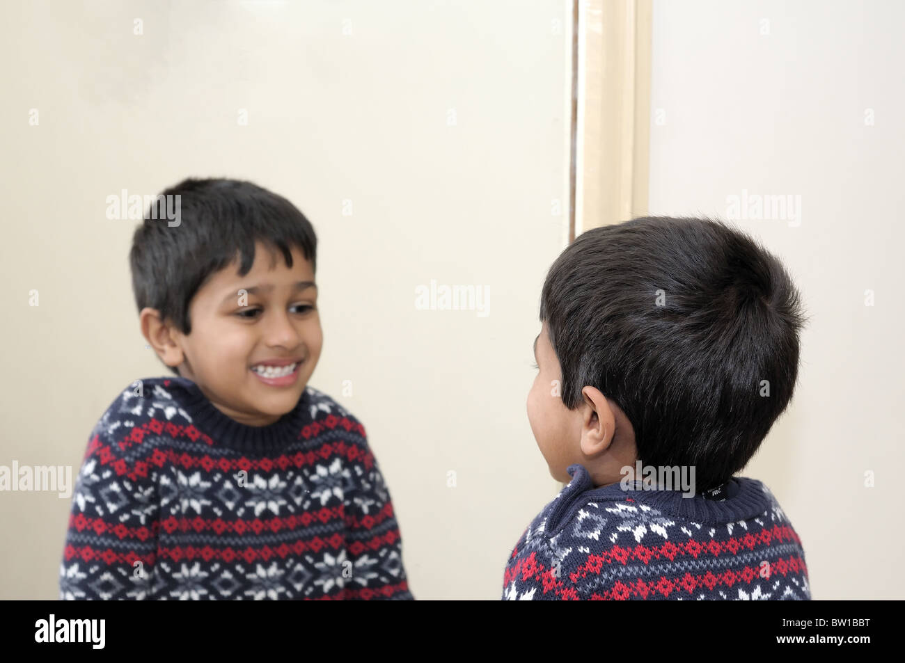 Cute toddler looking into mirror, laughing Stock Photo